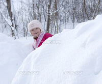 Smiling child looking out from a large pile of snow