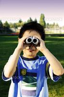 A boy looking through a binocular