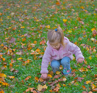 Curious young girl picking up a pine cone in the playground.