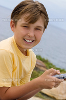 Child holding a portable game player and smiling to the viewer.
