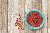dried Tibetan goji berries (wolfberries) in a blue ceramic bowl on a grunge white painted wood surface