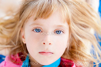 Beautiful blond blue eyes girl lying closeup face