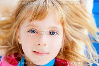 Beautiful blond blue eyes girl lying closeup face