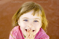 blond happy smiling little girl excited with hands in mouth