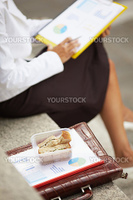 cropped view of business woman eating sandwich outdoors. Selective focus on sandwich
