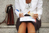cropped view of business woman eating sandwich outdoors. Selective focus on hand and pen