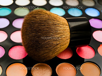 multicolored eye shadows with cosmetics brush against the white background