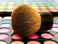 cosmetics brush over multicolored eye shadows against the white background