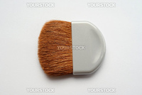A small makeup brush for applying powder on white background. Shallow depth of field.