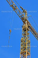 Detail of a yellow crane with hook against a blue sky