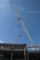 A White Tower Crane lifting an air conditioning unit on a consruction site