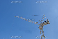 A White Tower Crane of a city construction site against a blue sky