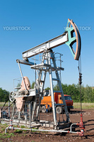 Oil pumping unit with  car service in the background