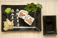 A set of sushi on a black plate with wasabi and gari, on a makisu (bamboo rolling mat).