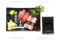 A set of sushi on a black plate with wasabi and gari, isolated on a white background.