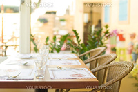 Tableware on table with series chairs. Restaurant in countryside