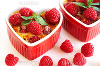 French creme brulee dessert with raspberries and mint covered with caramelized sugar in red  heart-shaped ramekins on white background
