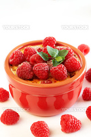 French creme brulee dessert with raspberries and mint covered with caramelized sugar in red terracotta ramekin on white background