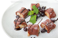 Sweet fruit roll with grapes dusted powdered sugar on white dish