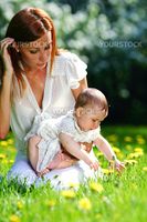 Happy mother and daughter on the green grass