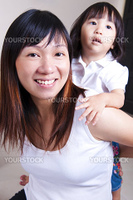Happy young mother playing with her daughter.