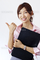 An Asian girl giving thumbs up sign and holding a file.