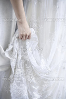 Bridemaid holding bride's wedding dress