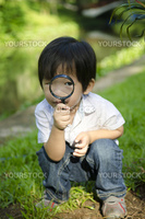 Little boy exploring nature by magnifier