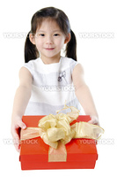 Little Asian girl arms out holding a beautiful wrapped present. Focus is on the ribbons.