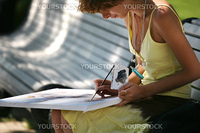 The girl draws a picture in park