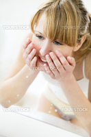 young woman washing her face in a basin and looking herself in the mirror