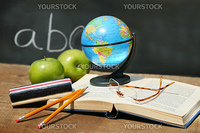 School books and apple in front of school chalkboard with small atlas
