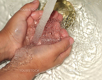 Close up of child holding his hands under running water in a sink.