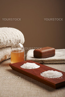 Spa salt, soap and shampoo with towels over a brown background