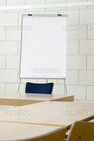 White empty billboard in a meeting room with tables and chairs