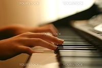 close-up of a piano player hands gently touching the keys
