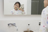 Reflection in Mirror of Girl Brushing Her Teeth