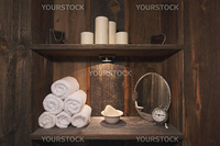 Rustic Spa Scene with Towels, Soap, Mirrors, Candles and Clock.