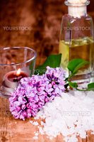 bath and spa items (oil, salt, lilac, candle) on wooden background