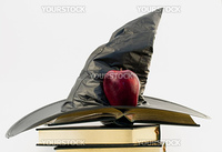 Witch's black hat and red apple atop open gilt edged, leather cover books against white background