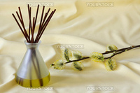 Wooden sticks in essential oil with yellow blooming branches