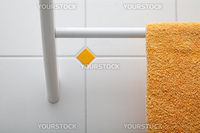 closeup of a towel holder on a tiled wall with a yellow towel