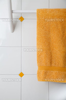 a towel holder mounted on a tiled wall with a yellow towel