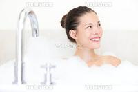 Bath woman enjoying bathtub with bath foam smiling happy. Mixed race Asian / Caucasian female model in bathroom.