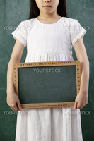 midsection of girl holding the blank black board