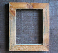 An empty wooden frame on a wooden wall.