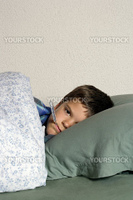 Sick child with thermometer, frustrated at his illness, resting in bed.