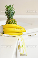 Bananas and ananas on white kitchen's table