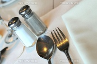Table layout with eating utensils and napkin.