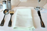 Restaurant table layout with white kitchen utensils before meals.